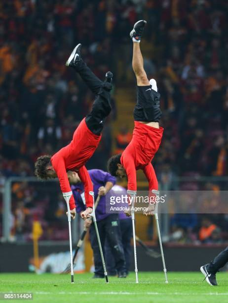 Players of Turkish Amputee National Football Team greet the supporters as they perform a handstand with crutches ahead of a Turkish Super Lig match...