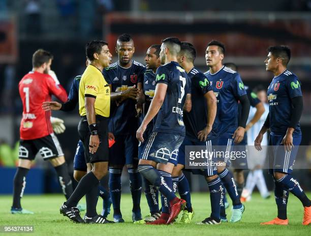 Players of Universidad de Chile argue with referee Enrique Caceres of Paraguay as he shows the red card to Lorenzo Reyes of Universidad de Chile...