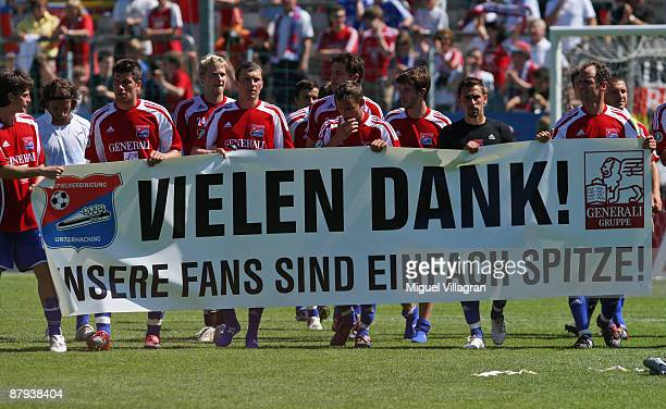 Players of Unterhaching hold a poster reading 'Thank you Our fans are the best' during the 3 Liga match between SpVgg Unterhaching and VfR Aalen at...