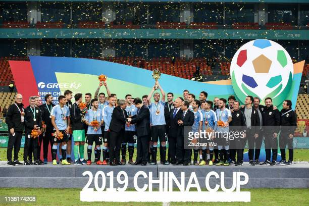 Players of Uruguay attend the award ceremony and Diego Godin rises up the trophy after 2019 China Cup International Football Championship between...