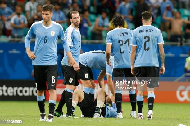 Players of Uruguay comfort teammate Luis Suarez after losing during a penalty shootout after the Copa America Brazil 2019 quarterfinal match between...