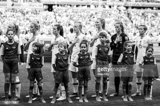 Players of USA line up during a national anthem prior to the 2019 FIFA Women's World Cup France Final match between The United State of America and...