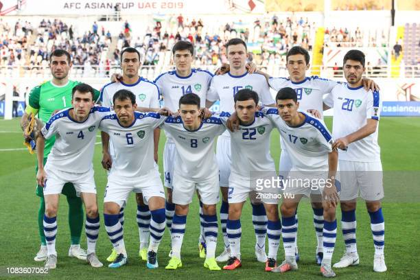 Players of Uzbekistan line up for team photos prior to the AFC Asian Cup Group F match between Japan and Uzbekistsn at Khalifa Bin Zayed Stadium on...