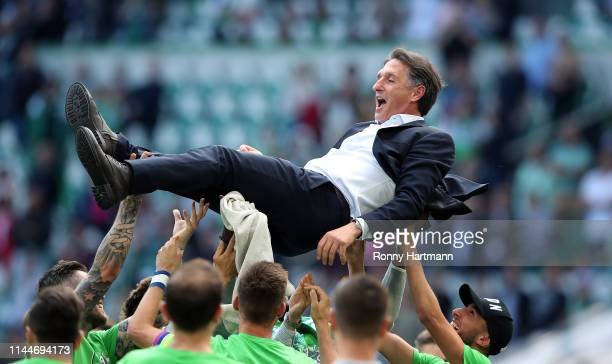 Players of VfL Wolfsburg throw head coach Bruno Labbadia into the air at the end of the Bundesliga match between VfL Wolfsburg and FC Augsburg at...