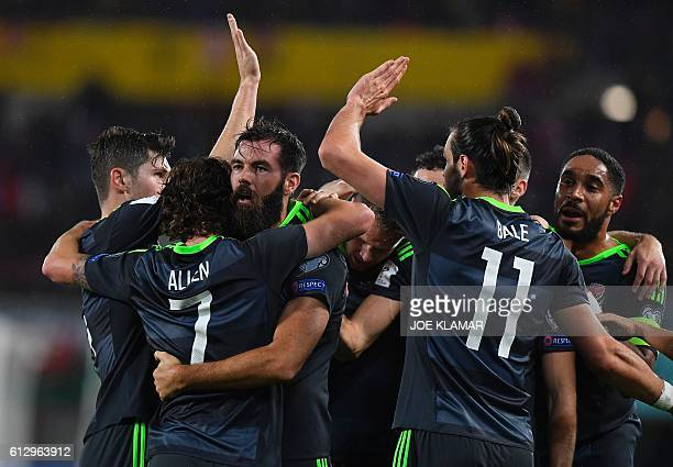 Players of Wales celebrate the opening goal during the WC 2018 football qualification match between Austria and Wales in Vienna on October 6 2016 /...
