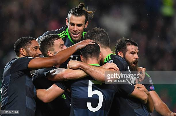 TOPSHOT Players of Wales celebrate their leasing goal to 21 during the WC 2018 football qualification match between Austria and Wales in Vienna on...