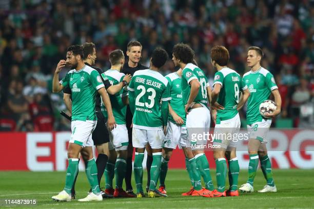 Players of Werder Bremen argue with a referee after the DFB Cup semi final match between Werder Bremen and FC Bayern Muenchen at Weserstadion on...