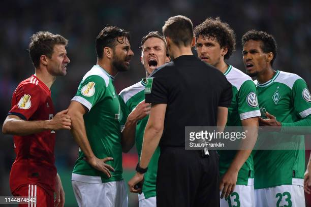 Players of Werder Bremen argue with referee Daniel Siebert during the DFB Cup semi final match between Werder Bremen and FC Bayern Muenchen at...