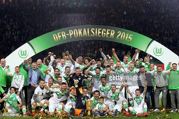 Players of Wolfsburg celebrate with the trophy following the DFB Cup Final match between Borussia Dortmund and VfL Wolfsburg at Olympiastadion on May...