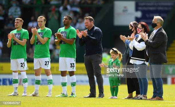 Players of Yeovil Town and Stockport County, alongside the family of Lee Collins, hold a minutes applause as a mark of respect to Yeovil Town...