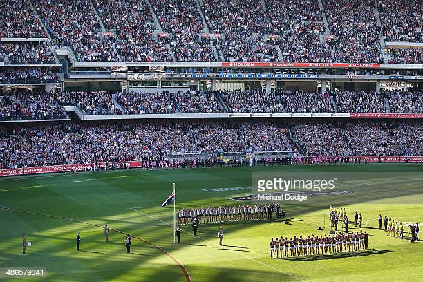 Players officals and fans stand for a minutes silence in tribute to Anzac Day during the round six AFL match between the Collingwood Magpies and the...