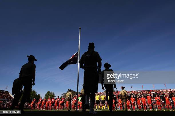 Players, officals and members of the Australian Army pay their respects during the Remembrance Day Ceremony during the round four BL match between...