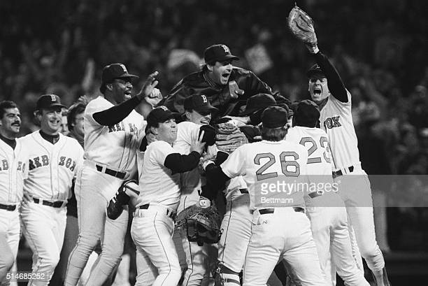 Players on the Boston Red Sox celebrate their American League championship victory, including Don Baylor , Bruce Hurst , Dave Stapleton , and playoff...