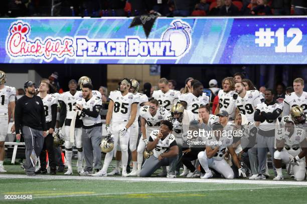 Players on the UCF Knights sideline react in the second half against the Auburn Tigers during the ChickfilA Peach Bowl at MercedesBenz Stadium on...