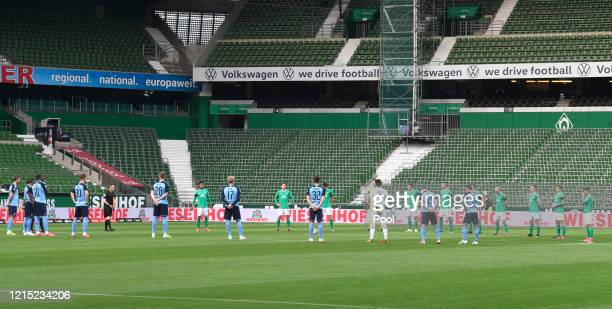 Players participate in a minute's silence for the victims of the coronavirus disease prior to the Bundesliga match between SV Werder Bremen and...