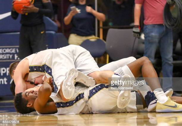 GW players pile on top of George Washington Colonials guard Yuta Watanabe after his apparent game winning three pointer with 4 seconds left during an...