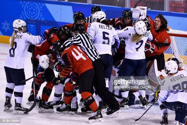 TOPSHOT Players pile up on the Canadian goal in the women's preliminary round ice hockey match between the US and Canada during the Pyeongchang 2018...