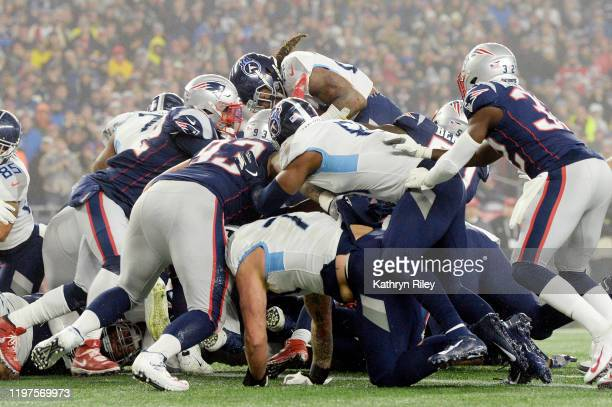 Players pileup as Derrick Henry of the Tennessee Titans scores a touchdown against the New England Patriots the second quarter of the AFC Wild Card...