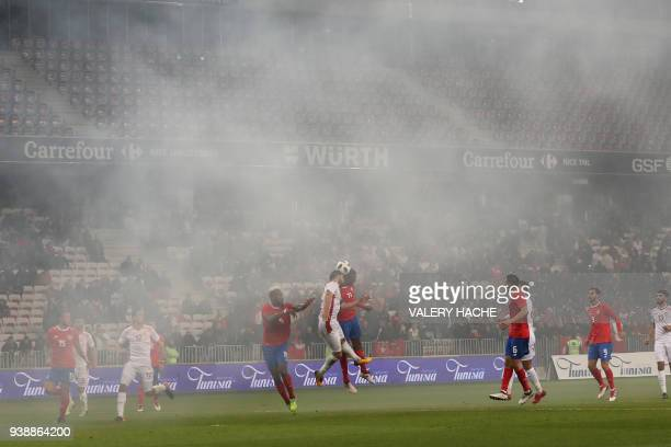 Players play as supporters burn flares causing smoke during the international friendly football match between Tunisia vs Costa Rica on March 27 2018...