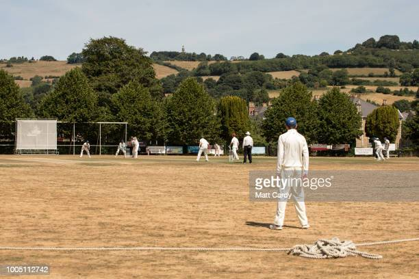 Players play on a parched cricket field during Lansdown Cricket Club vs Marshfield Cricket Club at Lansdown Cricket Club on July 25, 2018 in Bath,...