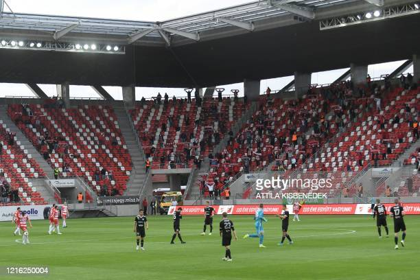 Players play on the field and supporters watch from the stands during the national championship's football match between DVTK and Mezokovesd in the...