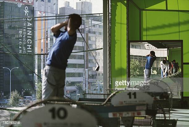 Players practice their golf swings at a city golf driving range on 15th October 1990 in the Ginza district in Tokyo, Japan.