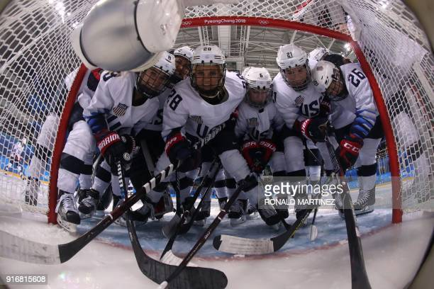 Players prepare for the start of their match against Finland in the women's preliminary round ice hockey match between Finland and the US during the...