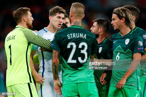 Players react after England's defender John Stones is confronted by Slovenia's goalkeeper Jan Oblak Slovenia's defender Aljaz Struna and Slovenia's...