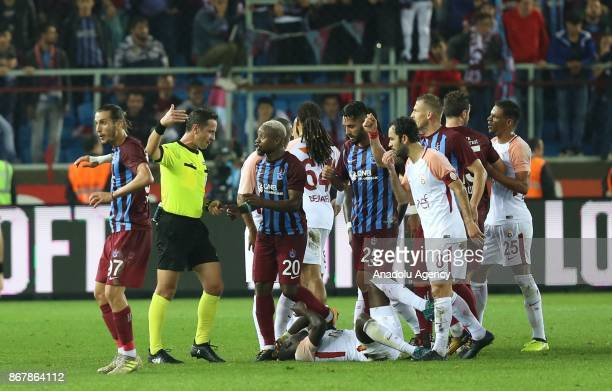 Players react after referee booked Feghouli of Galatasaray and Olcay Sahan of Trabzonspor with red cards during a Turkish Super Lig match between...