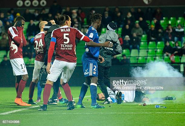 Players react after supporters have thrown a firecracker on the pitch during the French L1 football match between Metz and Lyon on December 3 2016 at...