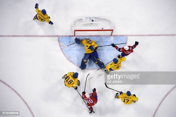 TOPSHOT Players react as a puck shot by Norway's Ken Andre Olimb bounces off Sweden's Viktor Fasth into the net in the men's preliminary round ice...