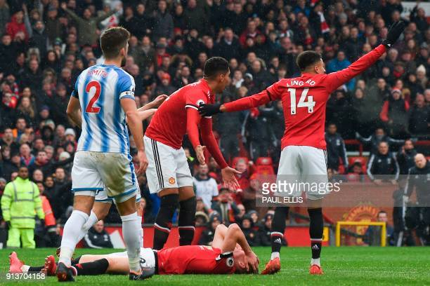 Players react as Manchester United's English midfielder Scott McTominay lies injured on the floor after colliding with Huddersfield Town's Swissborn...
