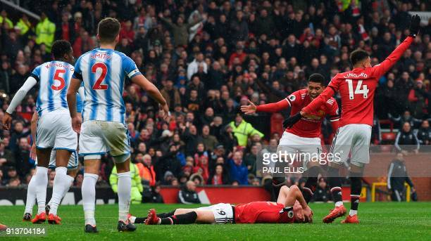 TOPSHOT Players react as Manchester United's English midfielder Scott McTominay lies injured on the floor after colliding with Huddersfield Town's...