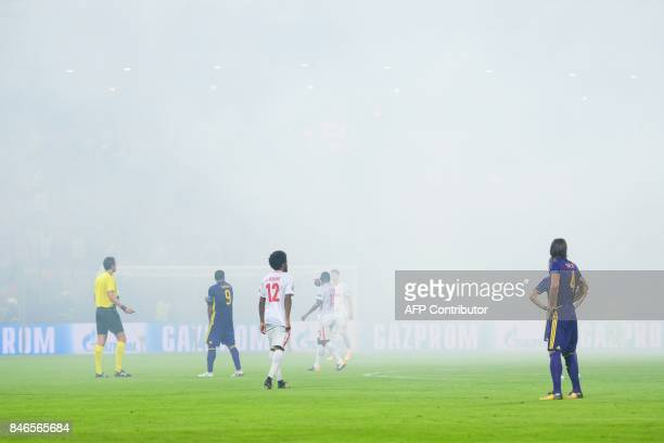 Players react on the pitch as supporters burn flares causing smoke during the UEFA Champions League Group E football match between NK Maribor and FC...