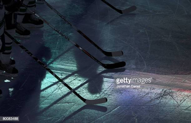 Players rest their sticks on the ice during the playing of the national anthem prior to the NHL game between the Chicago Blackhawks and the Vancouver...