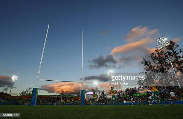 Players run onto the pitch as the sun sets during the Men's Rugby Sevens placing 78 match between France and Australia on Day 6 of the Rio 2016...