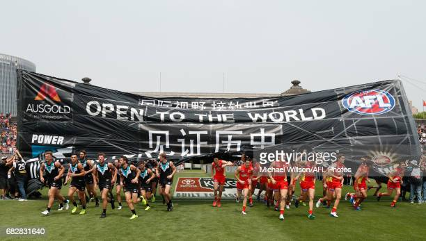 Players run through a joint banner during the 2017 AFL round 08 match between the Gold Coast Suns and Port Adelaide Power at Jiangwan Sports Stadium...