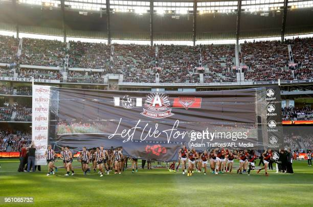 Players run through a joint banner during the 2018 AFL round five ANZAC Day match between the Collingwood Magpies and the Essendon Bombers at the...