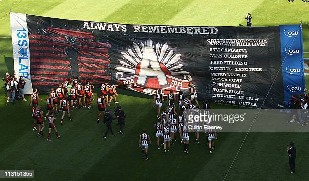 Players run through the banner during the ANZAC Day round five AFL match between the Essendon Bombers and the Collingwood Magpies at the Melbourne...