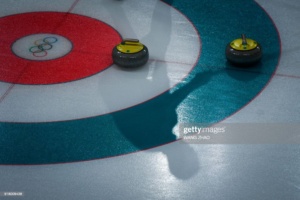 A player's shadow is seen on the ice surface during the curling men's round robin session between Switzerland and Britain during the Pyeongchang 2018 Winter Olympic Games at the Gangneung Curling Centre in Gangneung on February 14, 2018. / AFP PHOTO / WANG Zhao