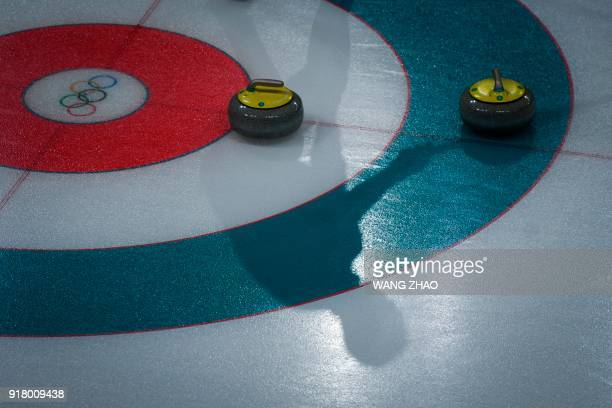 A player's shadow is seen on the ice surface during the curling men's round robin session between Switzerland and Britain during the Pyeongchang 2018...