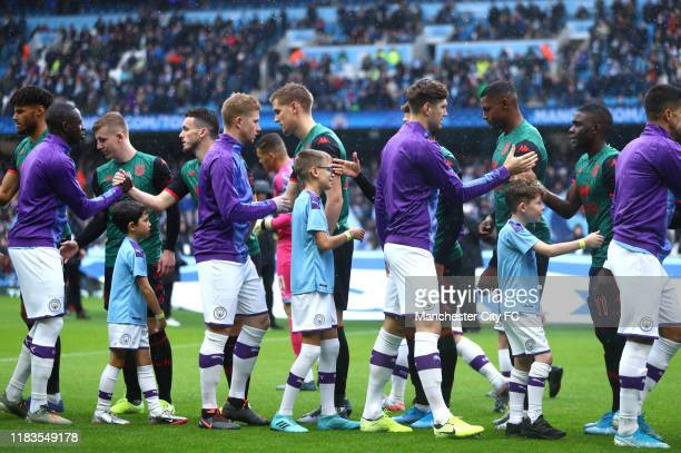 Players shake hands prior to the Premier League match between Manchester City and Aston Villa at Etihad Stadium on October 26 2019 in Manchester...