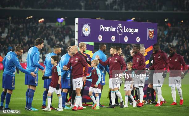 Players shake hands prior to the Premier League match between West Ham United and Leicester City at London Stadium on November 24 2017 in London...