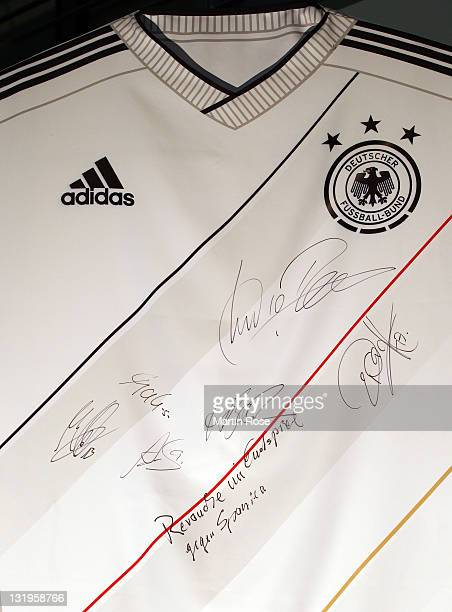 Players signed autographs on a jersey model after the Germany national team Euro 2012 jersey launch at Mercedes Benz Center on November 9 2011 in...