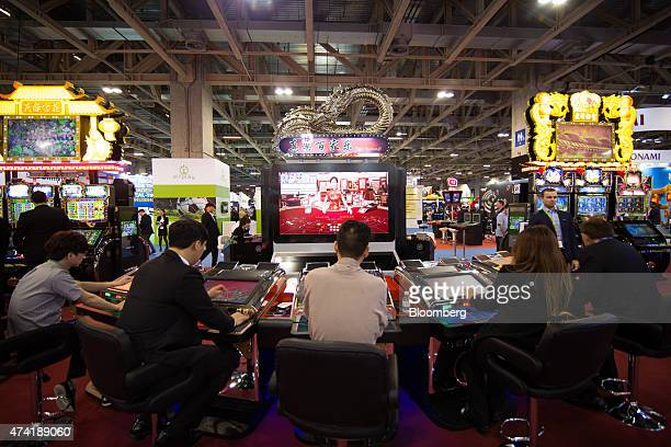 Players sit at an electronic baccarat gaming table at the Global Gaming Expo inside the Venetian Macau resort and casino operated by Sands China Ltd...