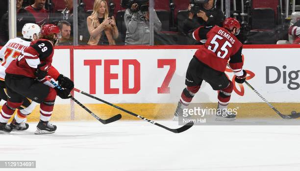 Players skate past a section of boards honoring hockey hall of famer Ted Lindsay during the third period of a game between the Arizona Coyotes and...