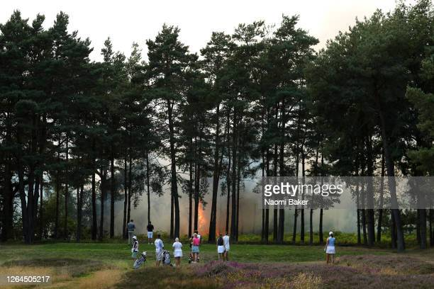 Players, Sophie Powell, Cara Gainer and Gabriella Cowley and their caddies look on as a fire nears the 10th hole during day three of The Rose Ladies...