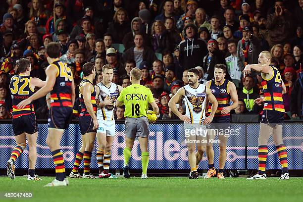 Players speak to umpire Ray Chamberlain after he mistakenly indicated that it was the end of the quarter when it was not during the round 17 AFL...