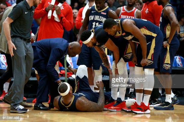 Players stand around DeMarcus Cousins of the New Orleans Pelicans after he injured his ankle during a NBA game against the Houston Rockets at the...