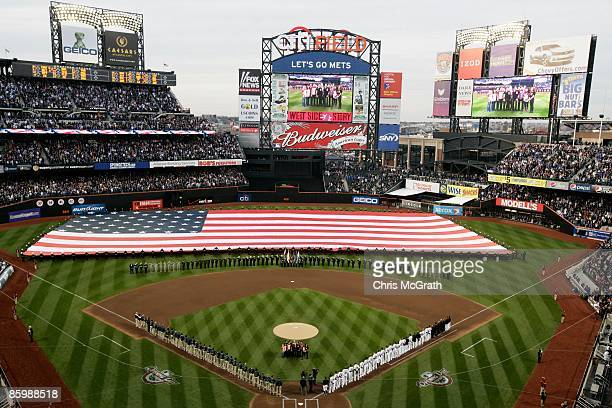Players stand at attention as the National Anthem is performed prior to the start of the opening day game between the San Diego Padres and the New...